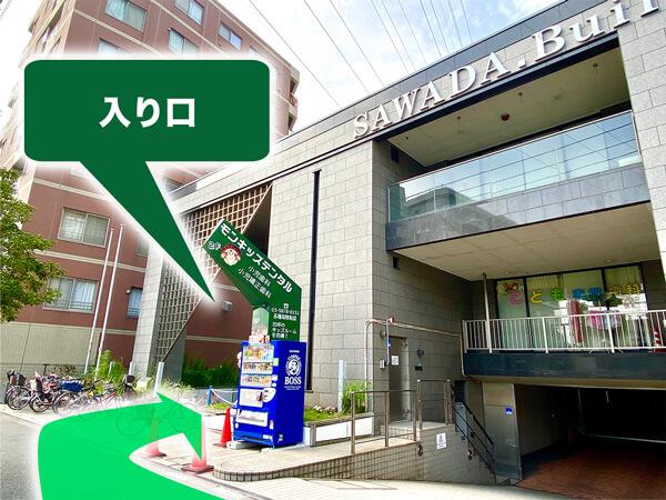 緑色の看板があるビルが当医院です